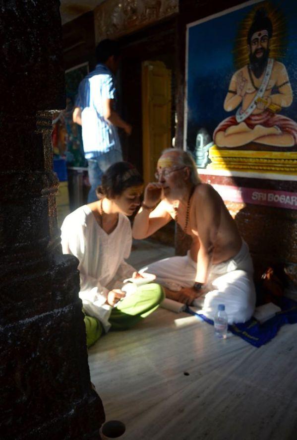 Nosso professor, Satchidananda, transmite o mantra do Siddha Boganathar à minha filha Marcela, no Templo de Palani. Uma pintura representando Boganathar aparece ao fundo.